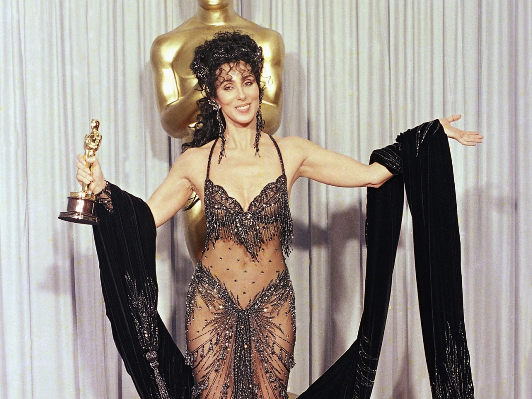 """Cher shows off both her Oscar and Bob Mackie black-sequined gown after winning the award for best actress for her role as the superstitious young widow of """"Moonstruck"""" at the 60th Annual Academy Awards, April 12, 1988 in Los Angeles. (AP Photo/Lennox McLendon)"""